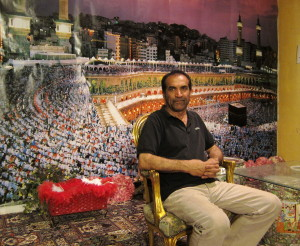 Hassan Dastgah in front of a photo of pilgrims in Mecca in a TV studio inside Silicon Valley's Burbank Theater where he had hoped to create programming for distribution in Iran, his birthplace.